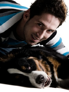 Young adult male with his dog on a white background